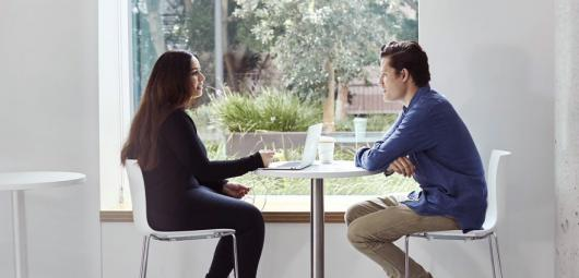 man and woman interview at a desk by the window