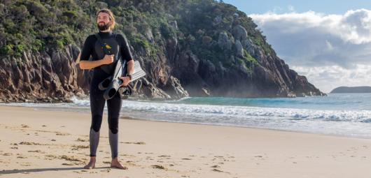 man in wetsuit on the beach