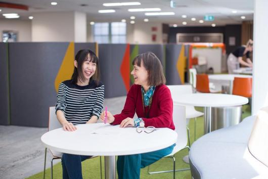 Two women sitting at a desk in a research area at UTS