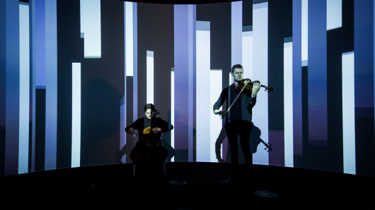 Two musicians playing in front of an artwork projection