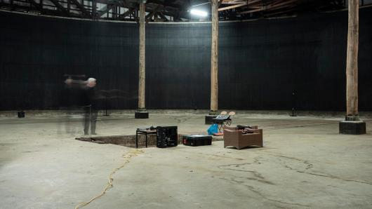 A person standing in a warehouse, with an installation set up in the middle