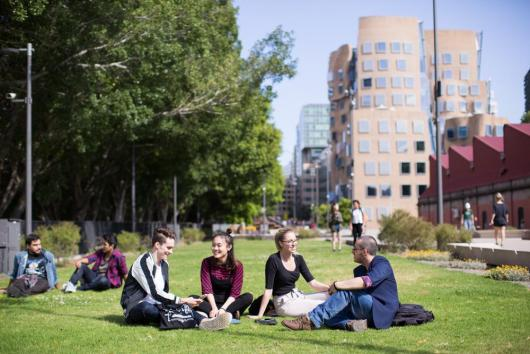 Students sitting on grass with UTS buildings in the background