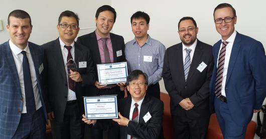 Group of academics and industry holding certificates and an award