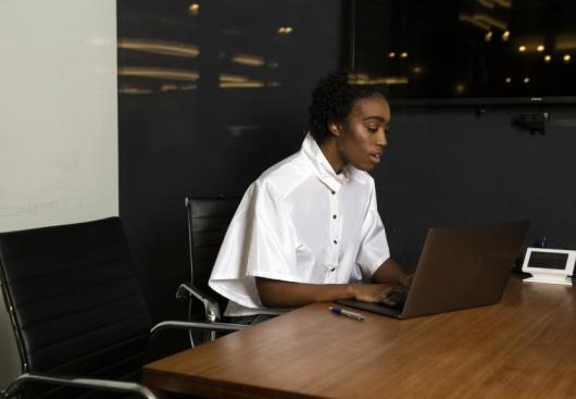 A non-binary person on a laptop at work
