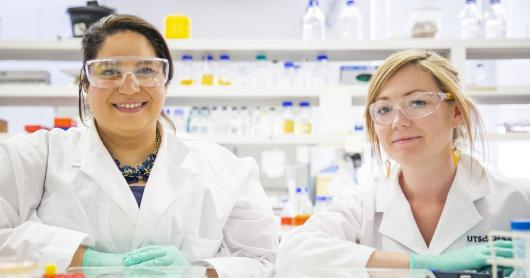 Two female science students sitting in lab environment wearing lab coats and protective goggles