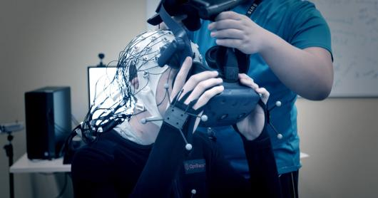 A person wearing a virtual reality headset with wires attached