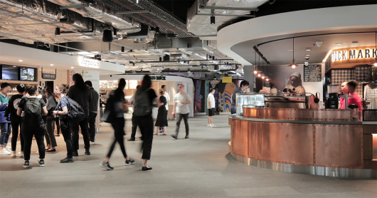 A brightly lit food court with neon signs and low, industrial ceilings filled with students