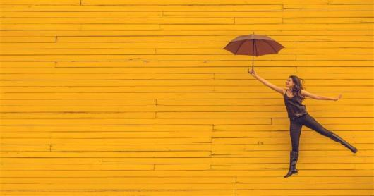 A person jumping up against a yellow wall, holding an umbrella