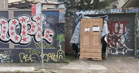 On a graffiti street, a light brown cupboard sits with a sign that says 'take what you need, leave what you can'