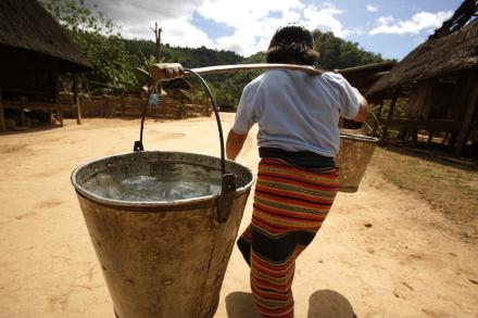 A woman in a rural village carrying buckets of water