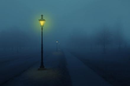 A street lamp glowing on a foggy night