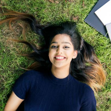 girl lying on grass with text books and tablet surrounding here