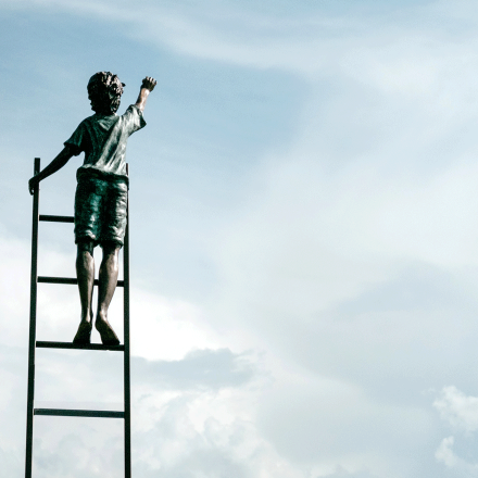 statue of child on ladder reaching toward the sky