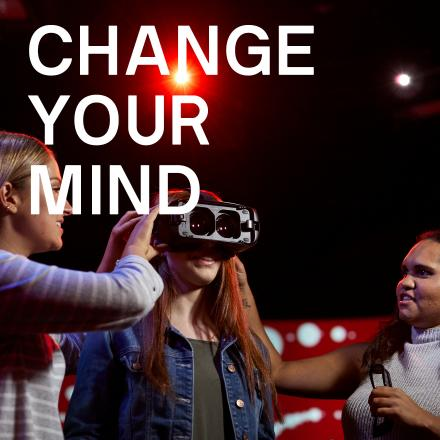 Three female students, one trying a Virtual Reality headset. Text: Change your mind
