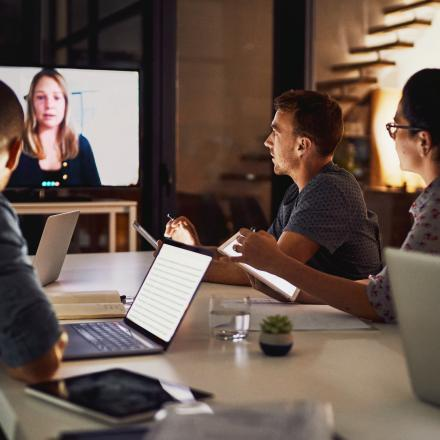 a group of colleagues sitting around a conference table and video conferencing with a person on a screen