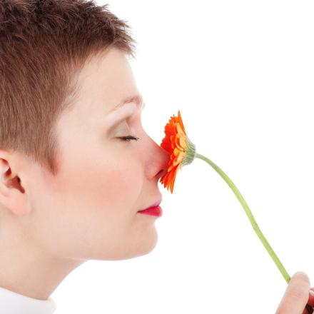 Woman smelling an orange flower