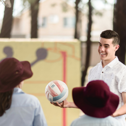 A male student teacher playing sport with primary students