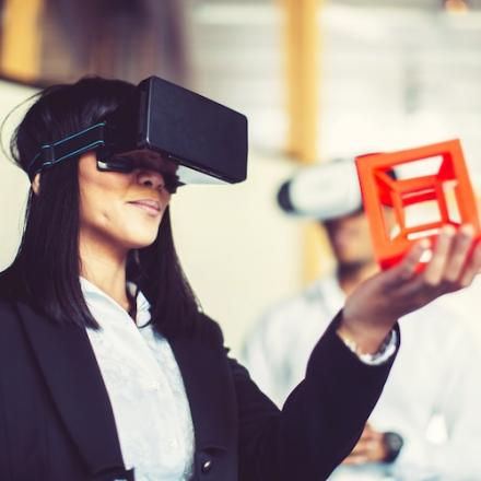 A female uses a 3D headset to view a hollow orange cube