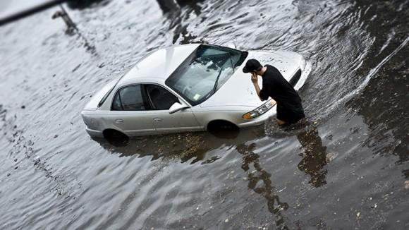 car and a man surrounded by floodwaters
