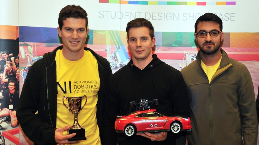 Three students from the University of Waikato. Student on the left is holding a trophy and student in the middle is holding a red racing car (their robot).