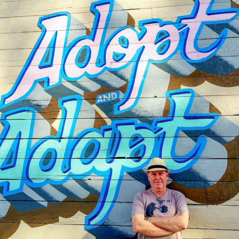 Dr Brent Jacobs standing in front of 'Adopt and Adapt' artwork