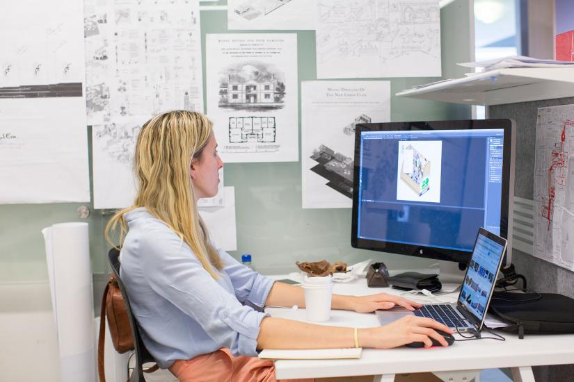 UTS student sitting at a computer with surrounded by architectural drawings
