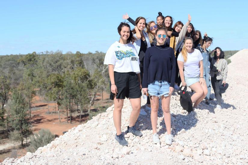 group of UTS students standing on a hill in the bush