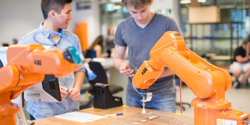 Students interact with robotic arms