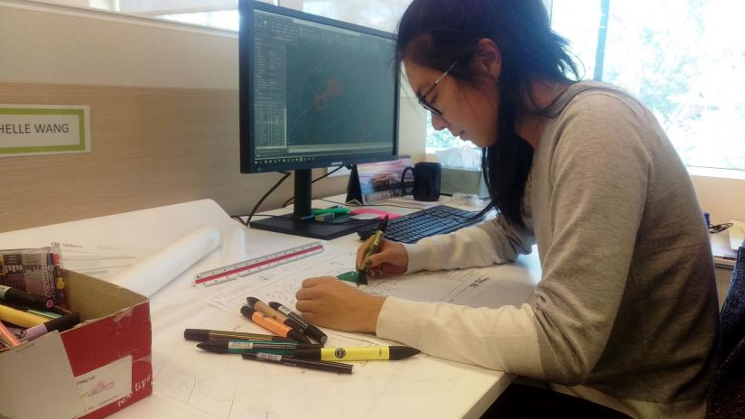 UTS landscape architecture student works at a desk with computer and drawing tools