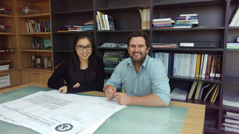 A man and woman at a desk with architectural drawings