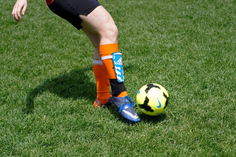 legs of a soccer player with shin pads and a soccer ball