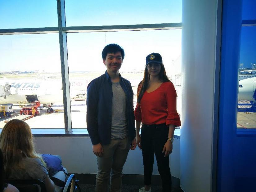 two students standing in front of a window at Sydney Airport. In the background, a Qantas plane is visible.