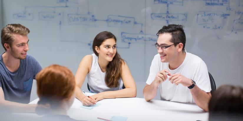 Five students in the Software development studio, sitting at a table and smiling. Behind them is a whiteboard wall