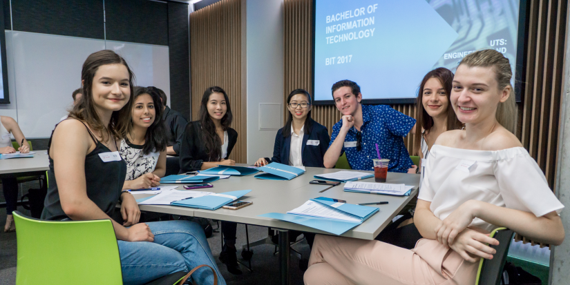 A group of students around a table learning about the BIT program