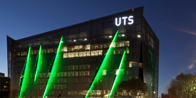 UTS Building 11 exterior at night showing the UTS logo and green building lights