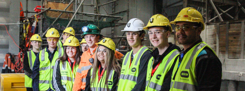 Students in hi-vis vests visit a construction site