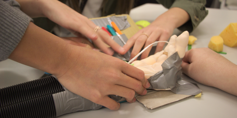A closeup of students building a prosthetic limb