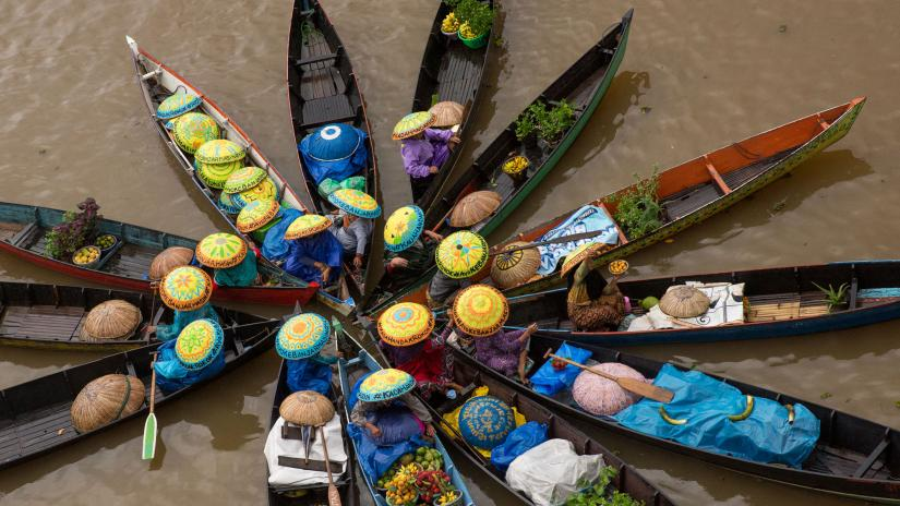 Circle of fruit selling boats on Banjarmasin's floating markets. The fruit sellers wear hats painted with anti-smoking messages.