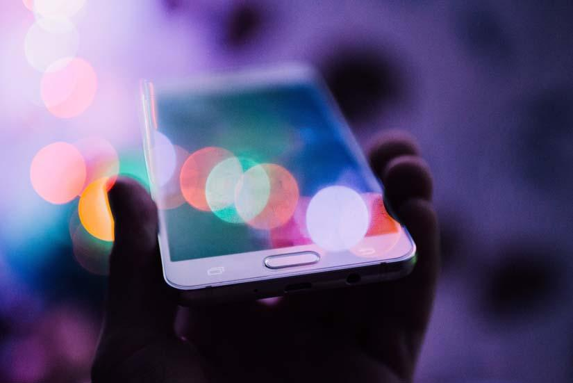 Hand holds a smartphone against a purple, light-flared background