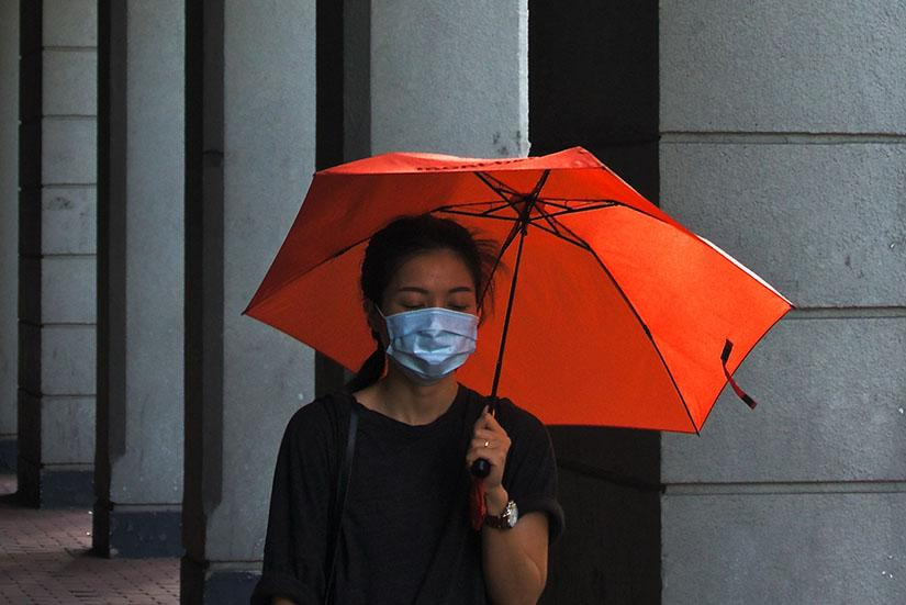 Chinese woman wears a respiratory mask, walks with red umbrella against a grey background