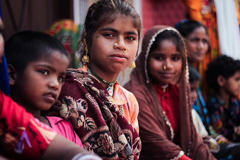 Children in traditional Indian dress sit outside a home, looking directly at camera