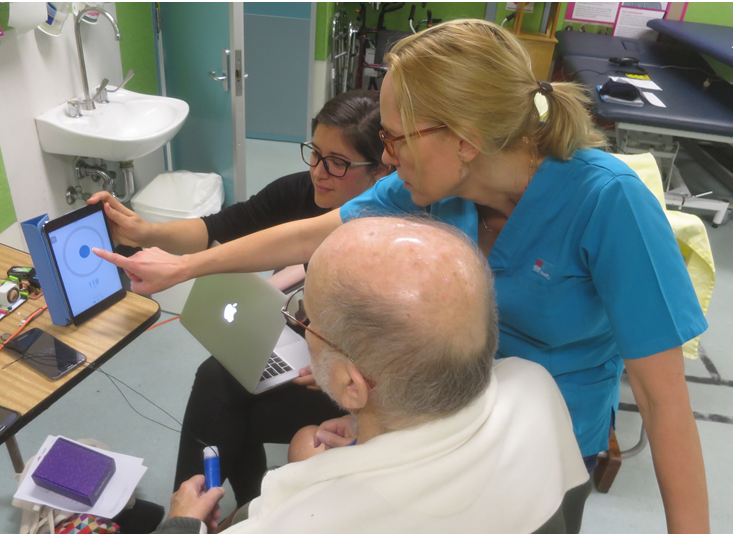 Female physiotherapist and female student point to digital screen, showing an elderly male patient the results of his stroke rehabilitation.