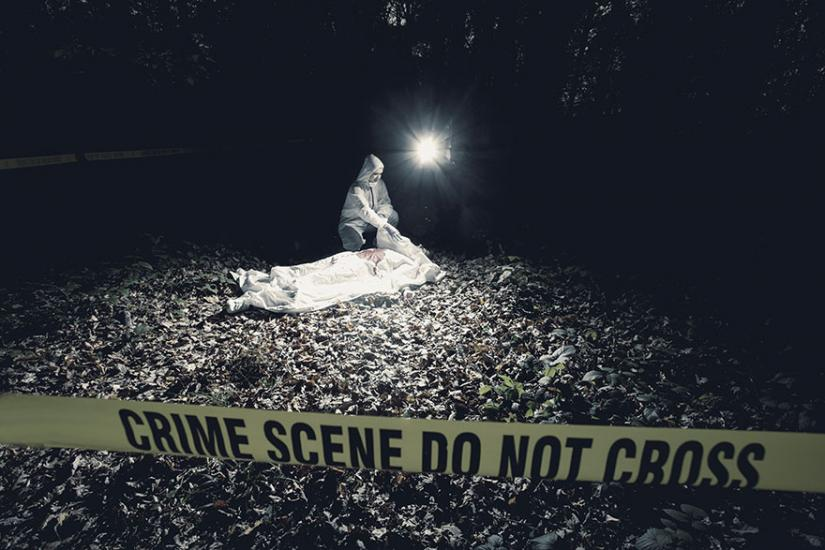 Beyond the yellow tape that reads crime scene do not cross is a crime scene investigator looking at body
