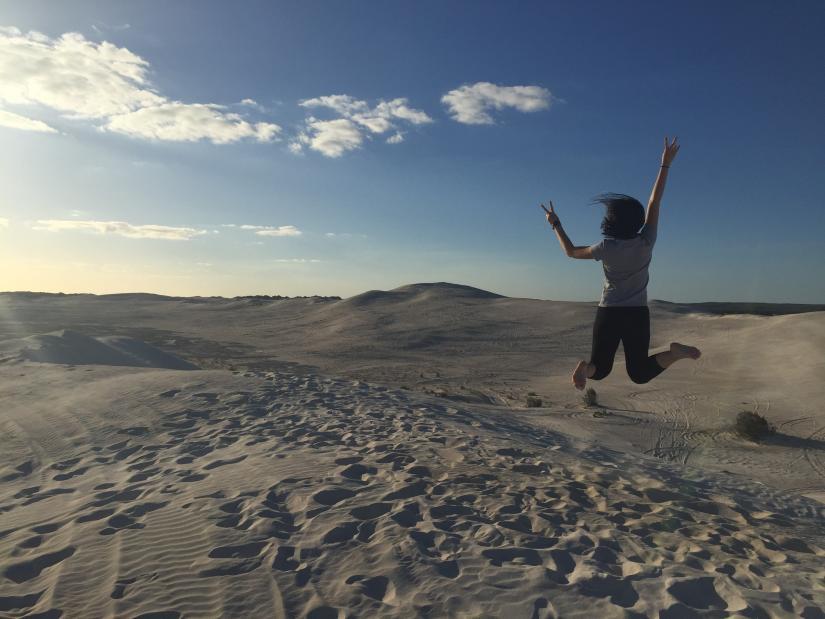 Female jumping in the sandy desert.