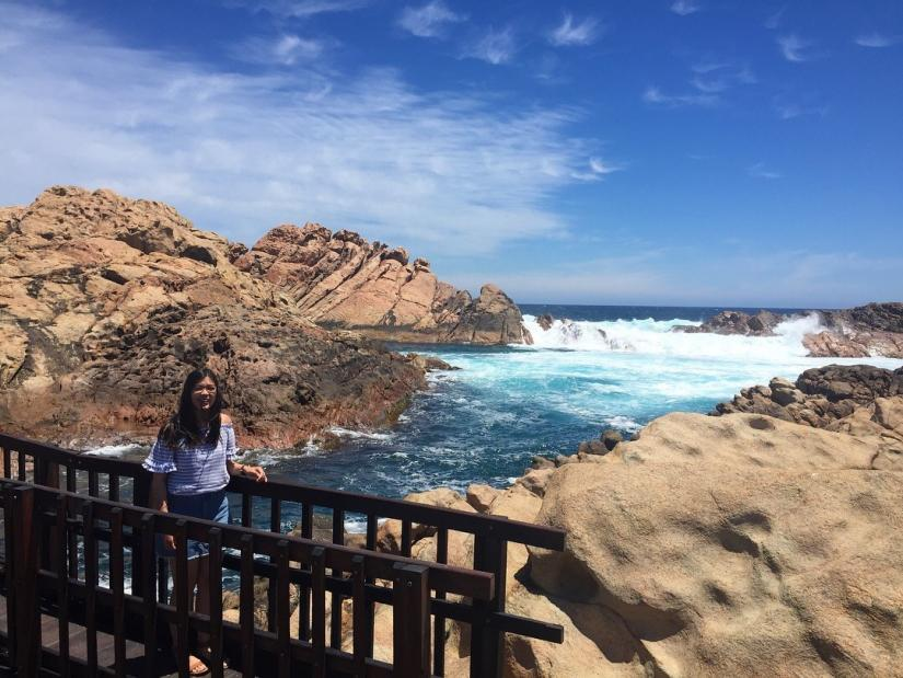 Orthoptics student Hong standing on bridge in front of the ocean
