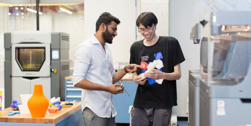 Two people discuss a 3D printed model that is in their hands