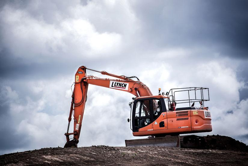 Orange-coloured construction equipment on top of a mound of dirt