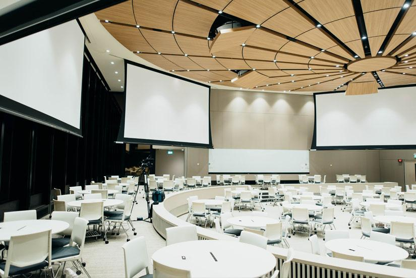 Modern conference room with screens on the walls and round tables across the floor.