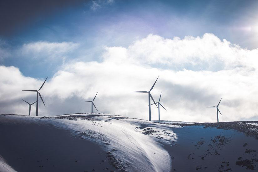 Windmills on top of a snowy mountain against a cloudy sky.