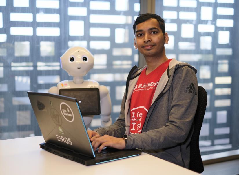 phD reseacher chand with social robot